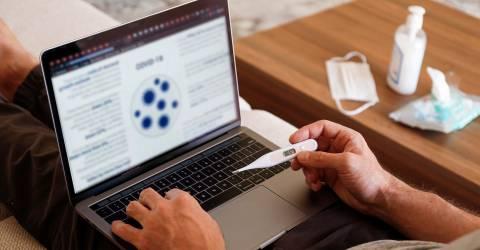 Beeld van ziek mens die vanuit huis werkt. Laptop op schoot met thermometer in hand. Op de tafel ligt een mondkapje, tissues en desinfectie handgel